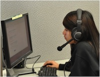 Female working on a computer wearing a headset.